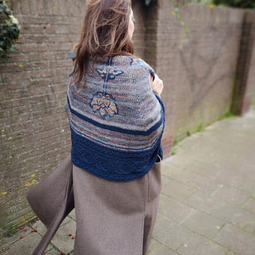 Hand knitted shawl with flowers on it worn by woman